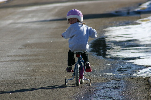 Child on bike with training wheels
